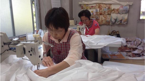 羽毛布団の裏にゴースをつけてミシンで縫製します